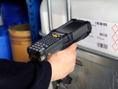 Human hand holding barcode scanner for scanning codes