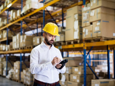 Warehouse worker or supervisor with barcode scanner. A mobile handheld PC with barcode scanner.